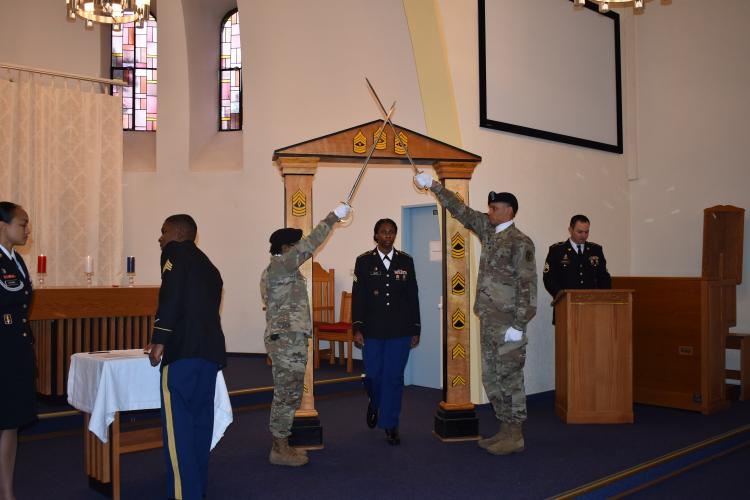 U.S. Army Sgt. Diane Cadet walks through the NCO arch Jan. 31 during an NCO Induction Ceremony at Landstuhl Regional Medical Center. (Photo Credit: Michelle Thum)