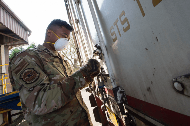 U.S. Air Force Airman 1st Class Andrew Cauley, a mail processing specialist with the USAFE- AFAFRICA Air Postal Squadron, Detachment Five, secures a transport truck as he prepares packages for transportation from RAF Alconbury, England on April 10, 2020. The Detachment Five postal team continue to maintain operational readiness during COVID 19 as the central postal distribution hub for U.S. service members stationed in the United Kingdom. (U.S. Air Force photo by Master Sgt. Brian Kimball)