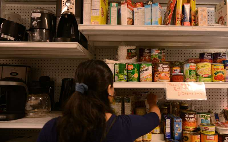 A military spouse picks canned goods being given away at the Airman's Attic at Ramstein Air Base, Germany, June 24, 2016. The services of the Airman's Attic are available to active-duty military personnel E-5 and below and their families. (U.S. Air Force Photo/ Airman 1st Class Joshua Magbanua)