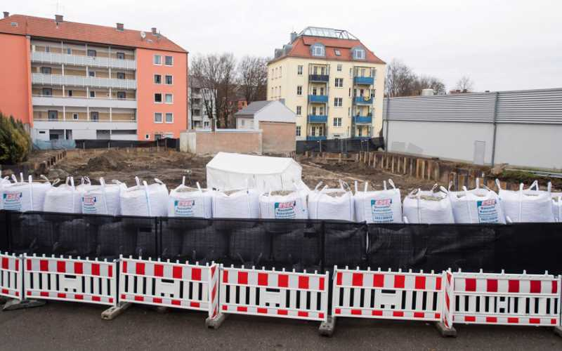 Sand bags and a fence are securing the location of the bomb site next to a construction site in Augsburg, Germany, Sunday Dec. 25, 2016. Tobias Hase/dpa via AP