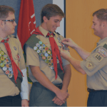 John Brandt, assistant scoutmaster for Boy Scout Troop 106 in Wiesbaden, Germany, pins the Eagle Scout badge on Adam Cloud of Wiesbaden, as fellow Eagle Scout badge recipient Michael Brandt, also of Wiesbaden, looks on, Sunday, Sept. 25, 2016.